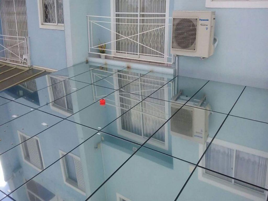 Cobertura de vidro em garagem de residência com película espelhada