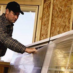 Homem trabalhando com vidro dentro de uma vidraçaria