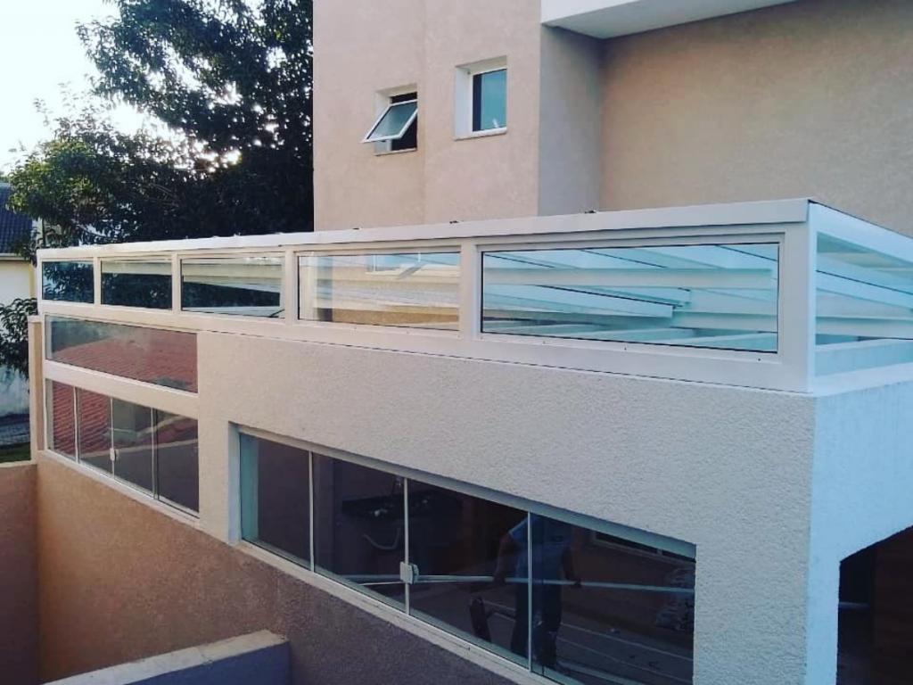 Cobertura de vidro fixa na garagem de um condomínio