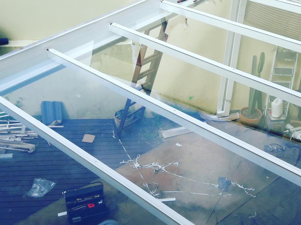 Cobertura de vidro retrátil com estrutura metálica instalada na garagem residencial
